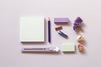 Notepad, cutter, colored pencil, clip, eraser on purple background. flat lay, top view, copy space. Work and study place