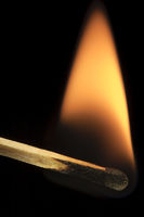 Macro close-up of burning wooden safety match isolated on black