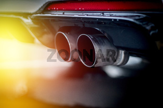 Powerful car with exhaust pipe, pollution and fine dust. Sunlight.
