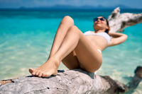 Pretty slim woman in white bikini sunbathe and relax on tropical beach.