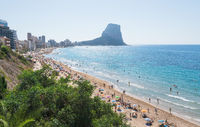 Sand beach with crowd of tourists for leisure along city of Calpe, Costa Blanca, Spain