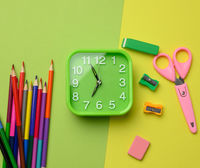 square green clock and stack of multicolored wooden pencils on a green background, top view