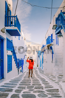 Mykonos Greece, Young woman in dress at the Streets of old town Mikonos during vacation in Greece, Little Venice Mykonos Greece
