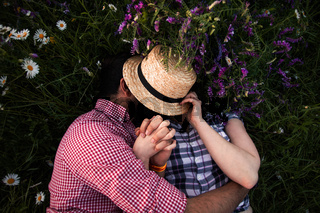 Romantic couple embracing in summer field with blooming wildflowers