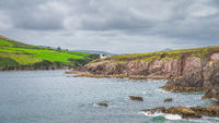 Dingle Lighthouse on the edge of the cliff with green fields in a distance