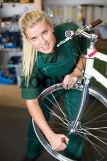 Fahrradmechanikerin repariert Fahrrad in einer Werkstatt