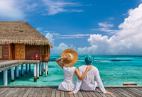 Couple in white on a tropical beach jetty