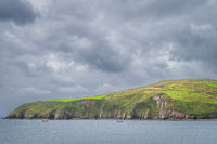 Fishing boats returning to Dingle village with green fields on tall cliffs