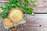 Bran flaxseed in bowl on old board top