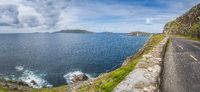 Large panorama with narrow winding road on the edge of cliff with archipelago of small islands in Dingle