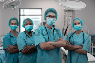 Diverse group of male and female doctors standing in operating theatre wearing face masks