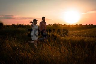 Lovely couple walking in the summer field