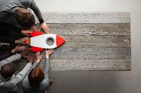 Creative team with startup rocket