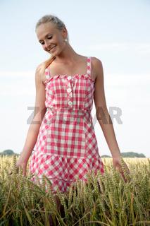 Junge Frau geht durch ein Kornfeld