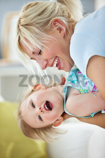 Simper mother playing with her daughter