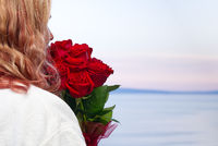 Happy woman in white robe with a bouquet of red roses looks from the hotel balcony at the sea