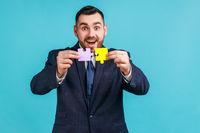 Excited bearded man wearing official style suit holding and showing two jigsaw pieces, matching and connecting puzzles, solving problems, creativity.