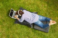 Freelancer Frau arbeitet am Laptop im grünen Garten