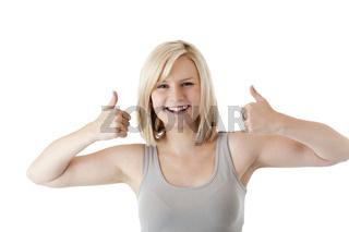 Schöne blonde Frau hält lächelnd beide Daumen nach oben