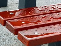 Raindrops on a bench, wet wooden boards. Detail