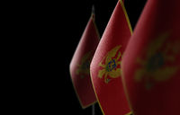Small national flags of the Montenegro on a black background