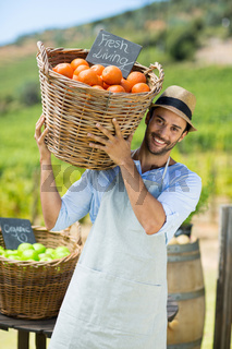Portrait of happy farmer carrying by fresh oranges in container