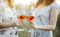 Two young women carrying goblet of alcohol cocktail with cherries and striped straw