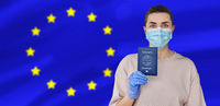 woman in mask and gloves holding immunity passport