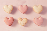 Delicious French macarons in heart shape on pink background