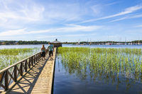 Young couple walking on a jetty in a lake