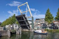 Motorboat passing opened bridge in Dutch medieval city Weesp