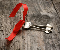 two metal house door keys with red ribbon on a woodenbackground