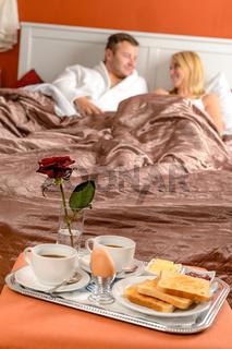 Happy couple lying bed romantic breakfast hotel