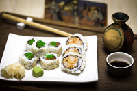 An elegant square white plate with fresh, healthy gourmet maki sushi sliced rolls made of rice, raw salmon and tuna fish, expensive green caviar, sesame seeds, nori and fried tempura prawn with strong wasabi, pickled ginger, a bowl of soy sauce and wooden