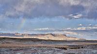 arid desert landscape with a rainbow