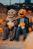 A guy with a pumpkin head sits next to a scarecrow