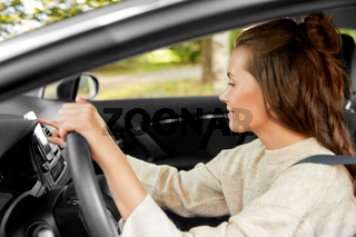 smiling woman or female driver driving car in city