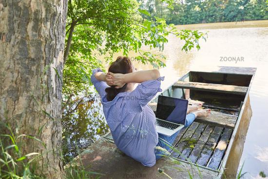 Frau mit Laptop in einem Boot am Seeufer im Urlaub