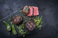 Traditional barbecue dry aged angus medaillon beef filet steak natural with herbs and red wine salt served as top view on a charred wooden board with copy space