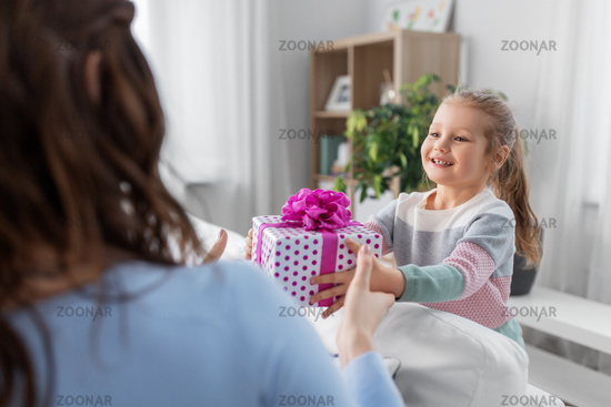 happy daughter giving present to mother at home