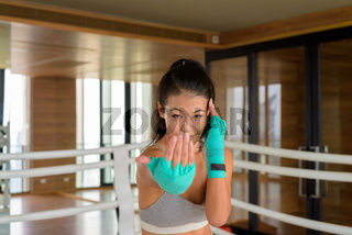 Asian woman kick boxer shadow boxing at gym and doing inviting gesture