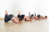 Group of young sporty sexy women in yoga studio, practicing yoga lesson with instructor, forming a line in Shishosana bent puppy dog asana pose. Healthy active lifestyle, working out indoors in gym