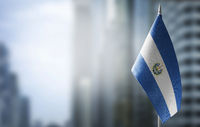 A small flag of Salvador on the background of a blurred background