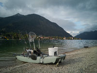 Fancy fishing boat on the beach with fishing rods, brailer and bucket on campground camping Walchensee in the alpine upland with lake and mountain Herzogstand in background