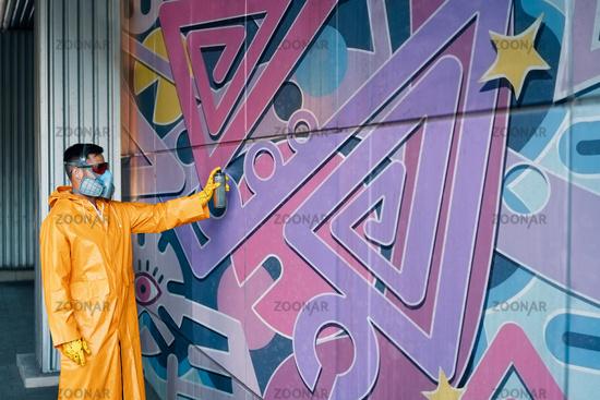 Street artist painting colorful graffiti on wall
