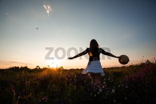 Girl enjoying freedom watching sunset in meadow