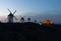 view of the windmills and castle of Consuegra in La Mancha in central Spain at sunset