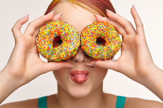 Teenager girl with unusual face art make-up . Child looking through holes in donuts  and showing tongue.