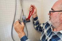 Heimwerker mit Rohrzange montiert neuen Brauseschlauch
