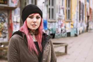 pierced and inked young woman in front of run-down graffiti covered houses